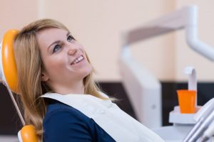 Calm female patient sitting in a dentist chair smiling