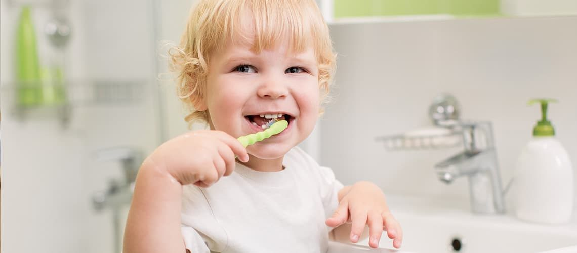 Happy child brushing his teeth