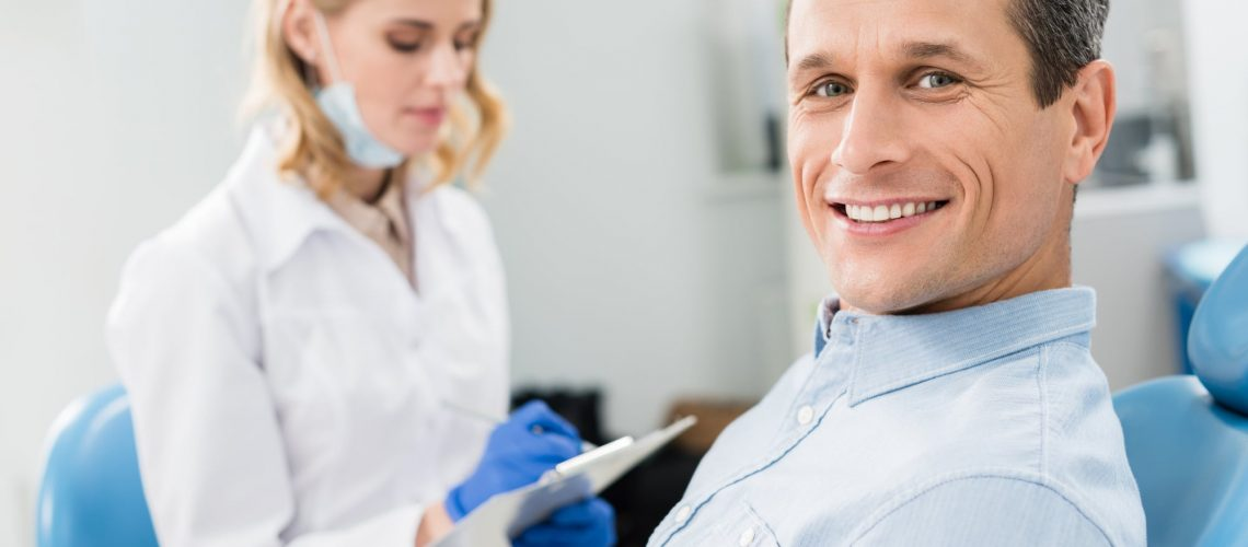 Smiling patient in a dentist chair with dentist in the background
