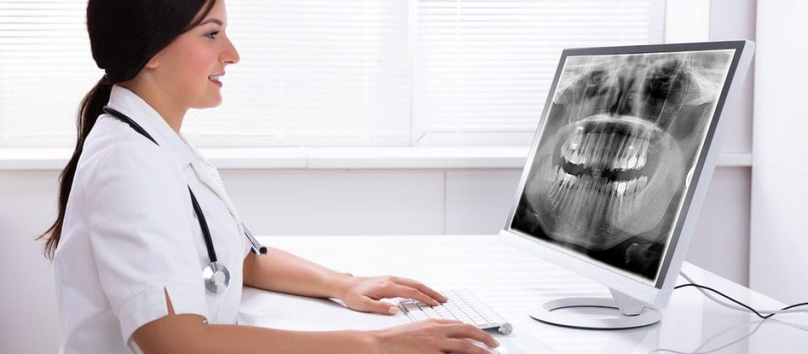 Dentist looking at a digital dental x-ray